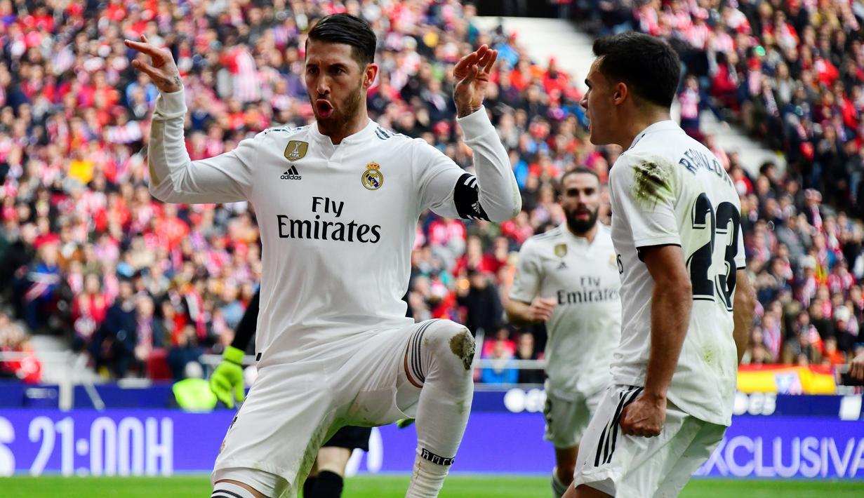 Bek Real Madrid, Sergio Ramos (kiri) berselebrasi usai mencetak gol ke gawang Atletico de Madrid pada pertandingan lanjutan La Liga Spanyol di stadion Wanda Metropolitano (9/2). Real Madrid menang 3-1 atas Atletico. (AFP Photo/Gabriel Bouys)
