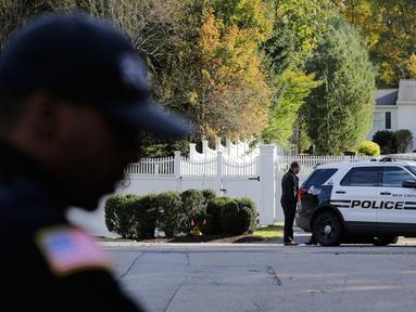 Aparat kepolisian berjaga di depan rumah mantan Menteri Luar Negeri Hillary Clinton dan mantan Presiden Bill Clinton di Chappaqua, New York, Rabu (24/10). Paket bahan peledak ditemukan di kotak surat kediaman Bill dan Hillary Clinton. (AP/Seth Wenig)
