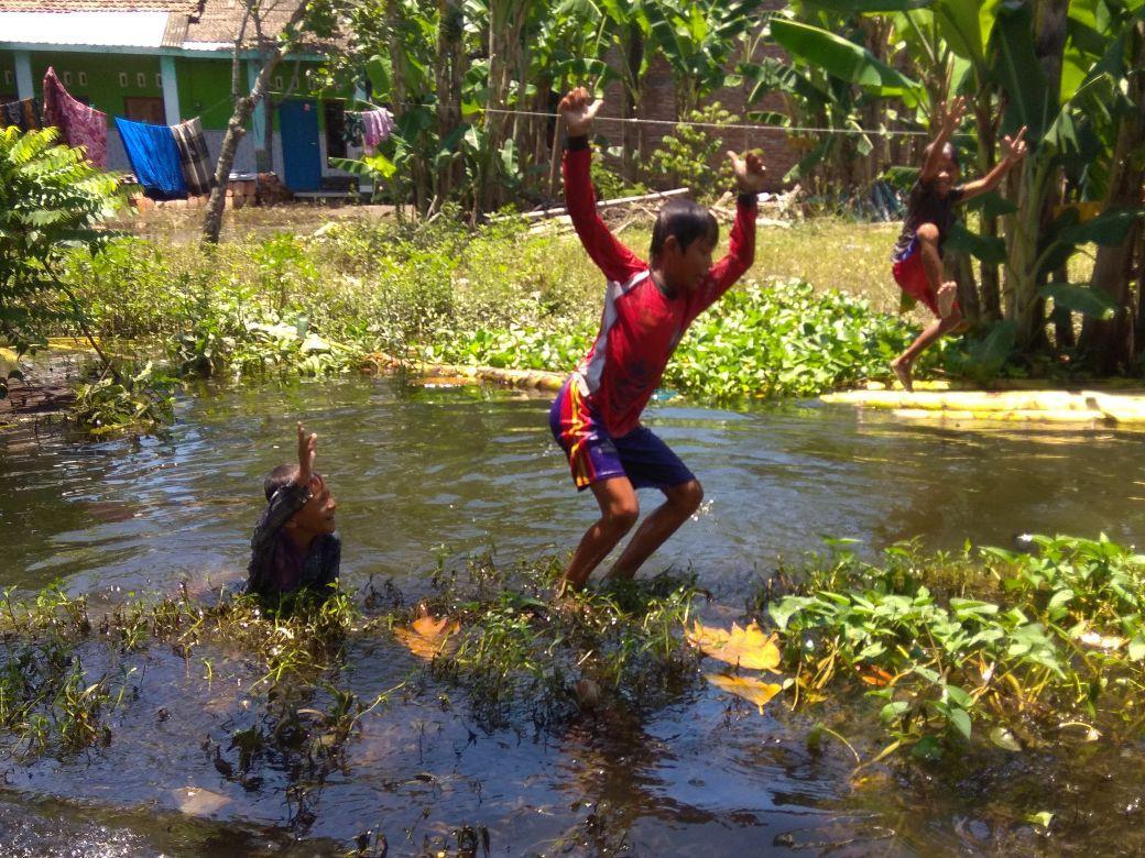 Anak-anak desa Kalisari bergembira dengan bermain dan mandi air banjir. (foto : Liputan6.com / edhie)
