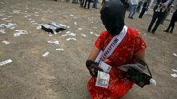 Wanita mengambil uang yang berjatuhan selama melakukan tetrikal dalam partisipasi mengungkap korupsi di Lima,Peru, (12/11/2015).  Mereka ingin menciptakan kepada masyarakat akan kesadaran tentang korupsi. (REUTERS/Mariana Bazo)