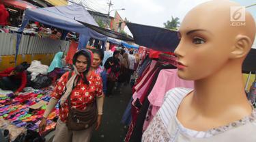 """Pembeli melihat dagangan PKL di Tanah Abang, Jakarta, Kamis (5/7). Ombudsman RI Perwakilan Jakarta Raya mengingatkan Pemprov DKI Jakarta, hanya PKL yang sudah divalidasi nantinya boleh berjualan di """"skybridge"""" Tanah Abang. (Liputan6.com/Angga Yuniar)"""