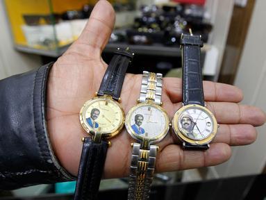 Seorang penjual menunjukan jam tangan yang bergambar mantan Presiden Irak, Saddam Hussein di Baghdad, Irak (28/12). Saddam Hussein adalah Presiden Irak yang menjabat sejak periode 16 Juli 1979 hingga 9 April 2003. (AFP/Sabah Arar)