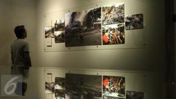 Pengunjung memperhatikan karya foto pada Roadshow pameran foto APFI di Galeri Foto Jurnalistik Antara, Jakarta, Minggu (9/10). APFI adalah bentuk penghargaan bagi foto-foto jurnalistik terbaik Indonesia yang digelar tahunan. (Liputan6.com/Gempur M. Surya)