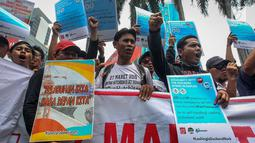Pekerja yang tergabung dalam Serikat Pekerja JICT berorasi saat menggelar aksi menutup jalan di depan gedung Kementerian BUMN, Jakarta, Rabu (13/3).  Mereka menuntut Kementerian BUMN segera memutus kontrak Hutchison di JICT. (Liputan6.com/HO/Asri)