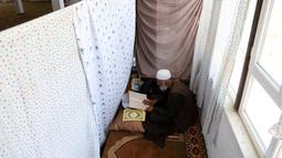Umat muslim Afghanistan membaca Alquran di sebuah masjid di Kabul, Rabu (6/6). Jamaah beriktikaf memperbanyak membaca Al-Quran, berzikir, doa dan istigfar pada sepuluh malam terakhir Ramadan menanti datangnya malam Lailatul Qadar. (AP/Rahmat Gul)