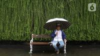 Seorang pria duduk sambil menggunakan payung saat hujan mengguyur kawasan Jakarta, Senin (3/2/2020). Diperkirakan sejumlah wilayah berpotensi diguyur hujan dengan intensitas lebat hingga disertai dengan angin kencang, kilat/petir hingga Rabu (5/2/2020) mendatang. (Liputan6.com/Angga Yuniar)