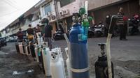 Antrean warga untuk mengisi ulang tabung oksigen di stasiun pengisian di kota Surabaya, Kamis (15/7/2021). Antrean yang terjadi di agen pengisian ulang oksigen itu disebabkan meningkatnya permintaan kebutuhan oleh warga. (Juni Kriswanto / AFP)