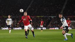 Bek Manchester United, Luke Shaw, berebut bola dengan pemain Derby Country pada laga babak kelima Piala FA di Pride Park Stadium, Kamis (5/3). Manchester United menang 3-0 atas Derby Country. (AFP/Oli Scarff)