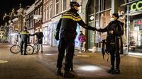 Polisi mengontrol sertifikasi keluar pada orang yang lewat saat jam malam dimulai di Haarlem, Belanda (23/1/2021). Belanda memasuki fase terberat dari pembatasan anti-virus Corona hingga saat ini. (AFP/ANP/Koen van Weel)