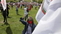 Seorang wanita memegang bendera serikat pekerja transportasi dan mengenakan masker saat memperingati Hari Buruh di tengah pandemi COVID-19 di Lisbon, Portugal, Jumat (1/5/2020). Aksi ini sudah mendapat persetujuan Kementerian Kesehatan dan Dalam Negeri Portugal. (AP Photo/Armando Franca)
