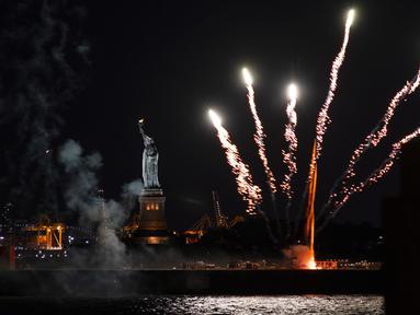 Kembang api yang diluncurkan dari tongkang meledak di atas Pelabuhan New York dan Patung Liberty di New York, Selasa (15/6/2021). Kembang api yang menandai berakhirnya pembatasan COVID-19 di seluruh negara bagian tersebut untuk menghormati para kelompok pekerja penting. (AP Photo/Craig Ruttle)