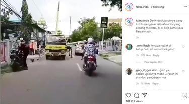 Sebuah video memperlihatkan detik-detik sebuah tiang listrik menimpa mobil yang sedang melintas di jalan.