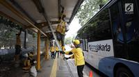 Bus Transjakarta melintas saat petugas Dinas Bina Marga Pemprov DKI mengecat bagian halte di Jalan Perwira, Jakarta, Jumat (5/1). Pengecatan dilakukan untuk menambah kenyamanan pejalan kaki dan pengguna Transjakarta. (Liputan6.com/Arya Manggala)