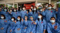 Tenaga medis mengenakan pita merah di seragamnya memberi hormat tiga jari di Rumah Sakit Umum Yangon di Yangon pada 3 Februari 2021 ketika seruan untuk pembangkangan sipil semakin meningkat menyusul kudeta militer yang menahan pemimpin sipil Aung San Suu Kyi. (STR / AFP)