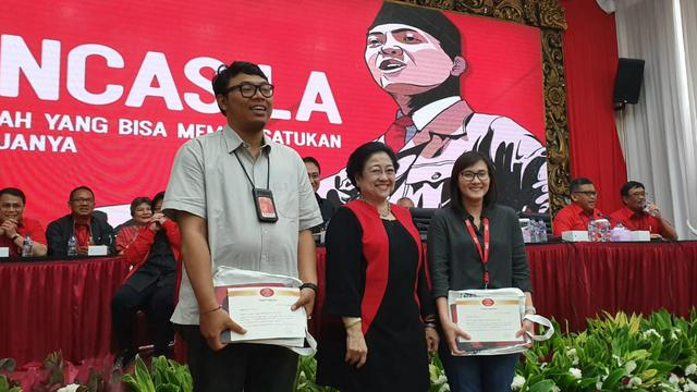 Ketua Umum PDIP Megawati Soekarnoputri memberikan buku kepada media, Senin (19/8/2019).