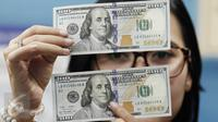 Teller menunjukan mata uang dolar AS di penukaran mata uang, Jakarta, Kamis (13/4). Nilai tukar rupiah terpantau menguat 0,09% atau 12 poin ke Rp13.263 per dolar AS di pasar spot. (Liputan6.com/Angga Yuniar)