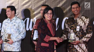 Menteri Keuangan Sri Mulyani (dua kanan) memberikan penghargaan Wajib Pajak 2019 kepada Direktur Keuangan BNI Anggoro Eko Cahyo di Jakarta, Rabu (13/3). Sri Mulyani memberikan apresiasi dan penghargaan kepada 30 Wajib Pajak (WP). (Liputan6.com/JohanTallo)