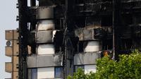 Kondisi bangunan apartemen Grenfell Tower di London usai kebakaran dahsyat, Minggu (18/6). Perkembangan terakhir menyebutkan 30 orang tewas dan lebih dari 70 residen masih hilang dalam insiden kebakaran apartemen 24 lantai itu. (TOLGA AKMEN/AFP)