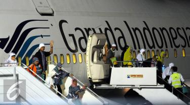 Ratusan jamaah Haji Indonesia embarkasi DKI Jakarta keluar dari pesawat saat tiba di Bandara Halim Perdanakusuma Jakarta, Selasa (29/9/2015). Sebanyak 440 jamaah dengan tiba sekitar pukul 18.30 WIB. (Liputan6.com/Helmi Fithriansyah)