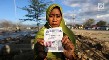 Seorang ibu bernama Lita, menunjukkan foto anaknya, Nanang Kosim (20) yang belum ditemukan pascagempa dan tsunami Palu di Pantai Talise, Sulawesi Tengah, Senin (8/10). Nanang diduga masih tertimbun di dalam tanah saat tsunami. (Liputan6.com/Fery Pradolo)