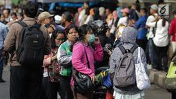 Antraen panjang masyarakat yang hendak menaiki bus Transjakarta di depan Cibubur Junction, Jakarta, Senin (16/4). Aturan ganjil genap tersebut diterapkan untuk mengurai kemacetan di ruas Tol Jagorawi. (Liputan6.com/Faizal Fanani)
