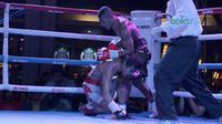 Petinju Indonesia, Jansen Marapu (tengah) memukul jatuh petinju Thailand, Phuttiphong Rakoon pada kelas Lightweight Mahkota Boxing Super Series di Cilandak Town Square, Jakarta (10/3/2018). Jansen menang TKO ronde ke sembilan. (Bola.com/Nick Hanoatubun)