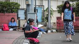 Sejumlah Mahasiswa IKJ Fakultas Seni Rupa duduk dipinggir jalan melukis suasana Bundaran HI, Jakarta Pusat, Kamis (19/10). Mereka melukis suasana Bundaran HI untuk mengaplikasikan ilmu yang didapatnya saat kuliah. (Liputan6.com/Faizal Fanani)