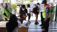 Calon penumpang mengantre saat pemeriksaan dokumen Surat Tanda Registrasi Pekerja (STRP) di Stasiun Tangerang, Banten, Senin (12/7/2021). Kementerian Perhubungan mengeluarkan aturan soal kewajiban membawa STRP dan/atau surat tugas bagi pengguna KRL. (Liputan6.com/Angga Yuniar)