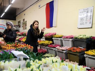 Seorang wanita mencari bunga jelang Hari Perempuan Internasional di pasar bunga di Moskow, Rusia (5/3). Hari Perempuan Internasional jatuh pada tanggal 8 Maret setiap tahunnya. (AFP Photo/Kirill Kudryavtsev)