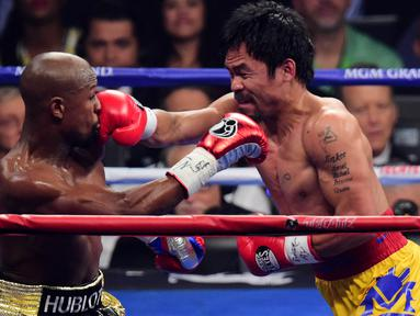 Petinju asal Filipina, Manny Pacquiao bertarung dengan lawannya asal Amerika Serikat. Floyd Mayweather saat pertandingan kelas welterweight di MGM Grand Garden Arena, Las Vegas, Nevada, Minggu (3/5/2015). (Joe Camporeale-USA TODAY)