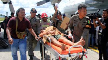 Korban selamat dari serangan Kelompok Kriminal Bersenjata (KKB) tiba di bandara di Timika, Papua, Kamis (6/12). Hingga hari ini, TNI-Polri telah menemukan 16 jenazah yang diduga merupakan pekerja PT Istaka Karya. (AP Photo/Mujiono)