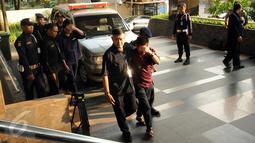 Petugas KPK membawa tersangka hasil OTT di gedung KPK Jakarta, Sabtu (20/6/2015). KPK mengamankan empat orang dari Kabupaten Musi Banyuasin saat sedang melakukan transaksi sebesar Rp 2,56 miliar pada Jumat (19/6) malam. (Liputan6.com/Helmi Fithriansyah)