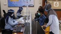 Petugas dengan mengenakan masker dan pelindung wajah melayani pemohon paspor di Kantor Imigrasi Kelas I Non TPI Tangerang, Senin (15/6/2020). Memasuki masa tatanan normal baru, pelayanan keimigrasian untuk warga mulai aktif kembali dengan menerapkan protokol kesehatan. (Liputan6.com/Angga Yuniar)