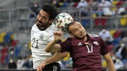 Gelandang Jerman, Ilkay Gundogan (kiri) berduel udara dengan gelandang Latvia, Arturs Zjuzins dalam laga uji coba menjelang Euro 2020 (Euro 2021) di Merkur Spiel Arena, Duesseldorf, Senin (7/6/2021). Jerman menang 7-1 atas Latvia. (AP/Martin Meissner)
