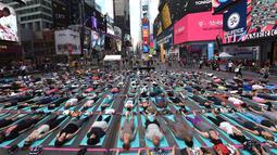 Warga ambil bagian berlatih yoga bersama di kawasan Times Square, New York pada 'Summer Solstice' atau hari dengan siang terpanjang di musim panas, Rabu (21/6). Acara itu menandai Hari Yoga Internasional yang jatuh pada 21 Juni. (TIMOTHY A. CLARY/AFP)