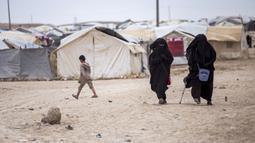 Dua wanita berjalan di Kamp al-Hol, Provinsi Hasakeh, Suriah, Sabtu (1/5/2021). Pejabat Kurdi mengatakan keamanan telah meningkat di kamp yang luas di timur laut Suriah, tetapi kekhawatiran berkembang dari wabah virus corona COVID-19 di fasilitas itu. (AP Photo/Baderkhan Ahmad)