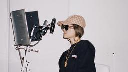 Kacamata rupanya jadi salah satu fashion item andalan Agnez Mo. Ketika sedang menjalani rekaman sebuah lagu, ia tampil swag dengan kaus panjang yang dipadukan dengan sepatu boot bermotif serta topi dan kacamata hitam.(Liputan6.com/IG/@agnezmo)