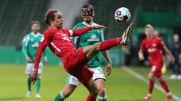 Striker RB Leipzig, Yussuf Poulsen (depan) mengontrol bola di depan bek Werder Bremen, Milos Veljkovic dalam laga semifinal DFB Pokal di Weserstadion, Bremen, Jumat (30/4/2021). RB Leipzig menang 2-1 atas Werder Bremen melalui babak perpanjangan waktu. (AFP/Cathrin Mueller/Pool)