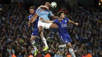 Bek Manchester City, Vincent Kompany, berbut bola dengan pemain Leicester City, Harry Maguire, pada laga  Premier League di Stadion Etihad, Senin (6/5). Manchester Citymenang 1-0 atas Leicester City. (AP/Nick Potts)
