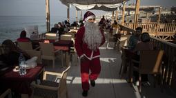 Seorang pramusaji Palestina berpakaian Sinterklas menggendong seorang anak untuk berfoto di sebuah restoran di pantai di Kota Gaza, Minggu (13/12/2020). Restoran tersebut didandani dengan tema Natal, pelayanannya pun berpakaian seperti Sinterklas. (AP Photo/Khalil Hamra)