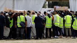 Pelayat membawa jenazah korban penembakan masjid untuk dimakamkan di Memorial Park Cemetery, Christchurch, Selandia Baru, Rabu (20/3). Setelah diserahkan kepada keluarga, sebagian jenazah akan segera dikebumikan. (AP Photo/Mark Baker)