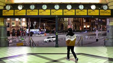Seorang pria berjalan keluar dari stasiun flinders street selama aturan jam malam di Melbourne, pada Selasa (17/8/2021). Kota terbesar kedua di Australia itu memberlakukan pembatasan tinggal di rumah pada pukul 9 malam hingga 5 pagi untuK meredam lonjakan Covid-19 varian Delta. (William WEST/AFP)