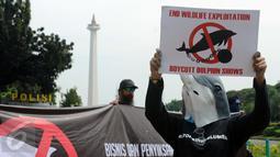 Aktivis JAAN membentangkan tulisan menolak eksploitasi hewan lumba-lumba di Jakarta, Senin (31/10). Mereka menilai pentas satwa lumba-lumba tidak menyampaikan pesan edukasi dan tidak menghargai . (Liputan6.com/Helmi Fithriansyah)