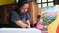 Puji Lestari, warga Padukuhan Kayu Balung, Kalurahan Girisekar, Kapanewonan Panggang, Gunungkidul, masih mampu menciptakan karya lukisan meski tak memiliki telapak tangan. (Liputan6.com/ Hendro Ary Wibowo)
