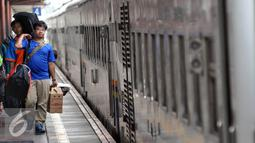Pemudik membawa barang bawaannya berjalan menuju pintu kedatangan saat tiba di Stasiun Senen, Jakarta, Sabtu (9/7). Puncak arus balik pemudik di stasiun Senen diperkirakan terjadi pada besok Minggu (10/7). (Liputan6.com/Johan Tallo)