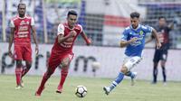 Striker Persib Bandung, Jonathan Bauman, berebut bola dengan pemain Arema FC, Muhammad Rafli, pada laga Liga 1 di Stadion GBLA, Jawa Barat, Kamis (13/9/2018). Persib menang 2-0 atas Arema FC. (Bola.com/M Iqbal Ichsan)