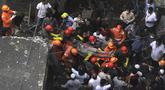 Petugas membawa korban yang selamat dari puing-puing bangunan tempat tinggal tiga lantai yang runtuh di Bhiwandi, India, Senin (21/9/2020). Sepuluh orang tewas dan sekitar 25 lainnya dikhawatirkan masih terjebak setelah bangunan itu runtuh sebelum fajar saat para penghuni terlelap tidur. (AFP)