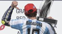 Valentino Rossi mengenakan jersey tim sepak bola Argentina saat merayakan kemenangkan MotoGP di sirkuit Termas de Rio Hondo, Argentina  pada April 2015. (AFP/Juan Mabromata)