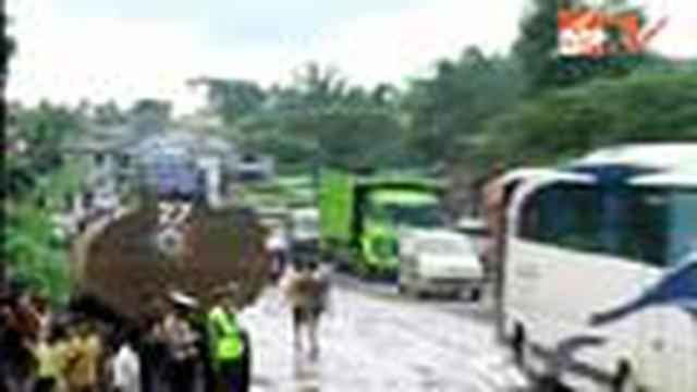 Kondisi jalan yang rusak membuat bus dan truk melintasi jalur secara bergantian. Jalan rusak di Kedaton, Bandar Lampung, sepanjang puluhan kilometer.
