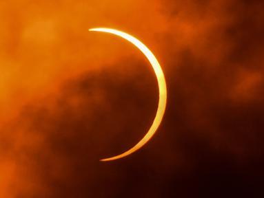 Bulan bergerak di depan Matahari saat berlangsungnya gerhana matahari cincin (Annular Solar Eclipse) yang terlihat dari langit New Delhi, india, Minggu (21/6/2020). Sebagian penduduk Bumi bisa menyaksikan fenomena langka, Gerhana Matahari Cincin. (Jewel Samad / AFP)